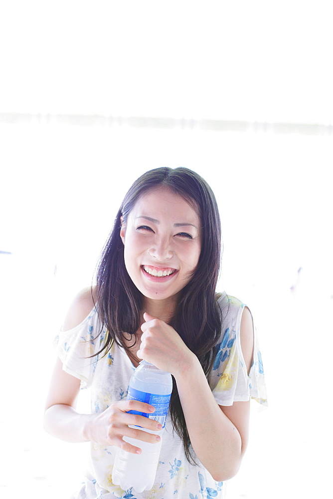 Japanese woman holding a bottle of water and smiling at camera