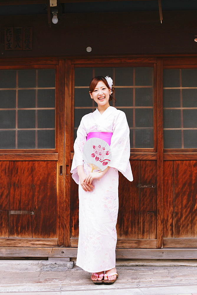 Japanese woman in Yukata holding a traditional paper fan