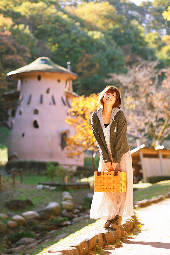 Japanese woman with short hair holding a basket and looking at camera