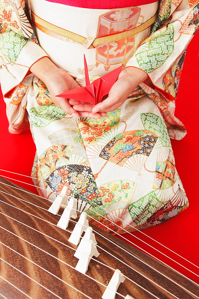 Close up of a Japanese woman in a kimono holding an origami of a crane next to a koto