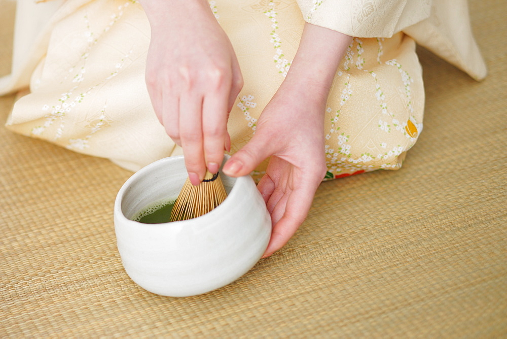 Woman Whisking Herbal Tea in Bowl