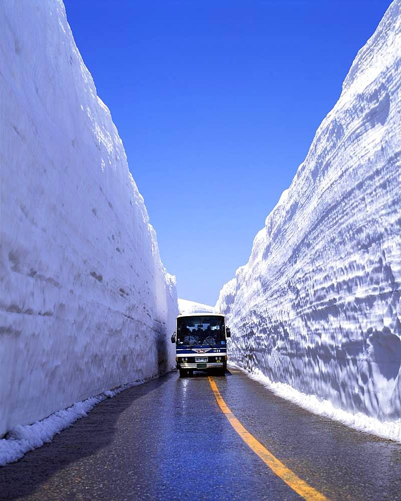 Bus on snow-banked road, Toyama, Japan