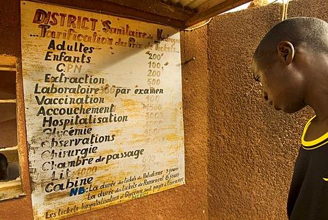 Man watching prices on medical clinic sign, Kedougou, Senegal