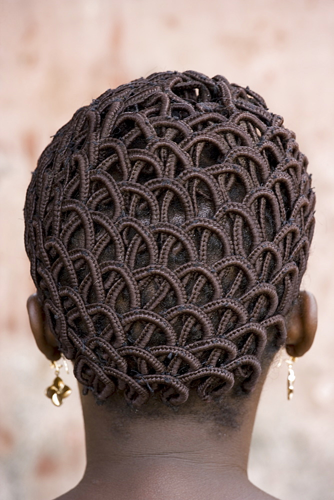 A woman's head with braided patterned hair and earrings, Benin, Africa