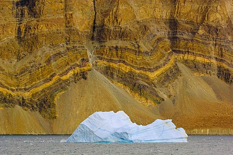 Iceberg and fjord walls with sedimentary layers, Scoresby Sound, East Greenland
