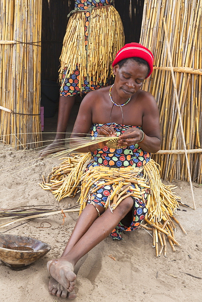 At the visitor village Lizauli you can gain an insight into the traditional way of life of the Mbukushu, Caprivi Region, Namibia - here a woman weaving raffia