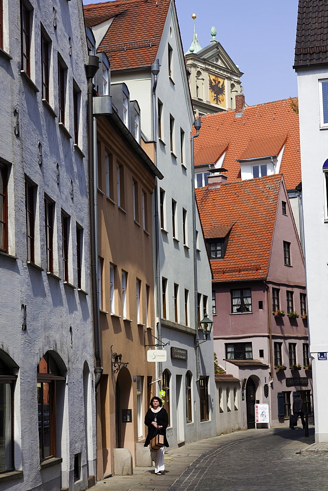 Woman walking in alley at Pfladergasse, Augsburg, Bavaria, Germany