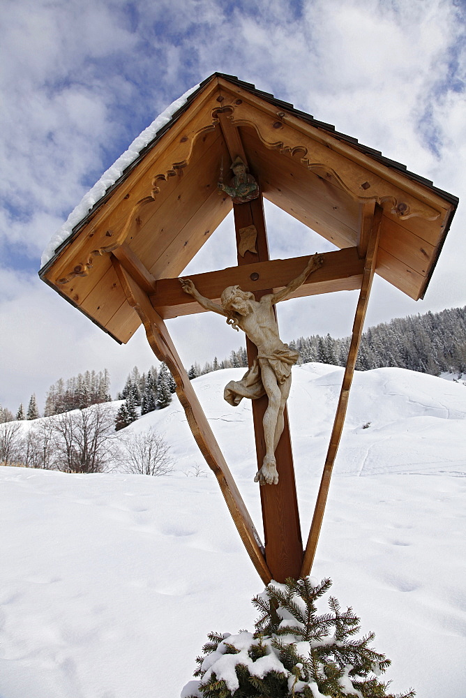 Close-up of shrine with crucifix in snow, South Tyrol, Italy