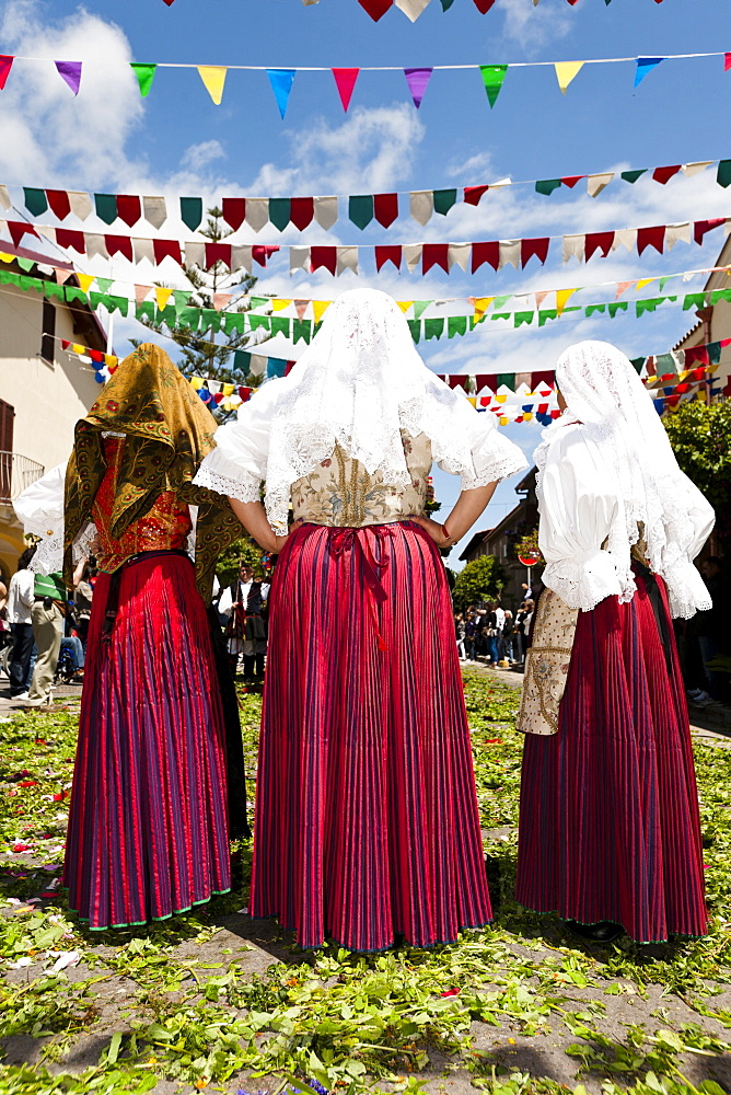 Three woman in costume for procession of Sant 'Efisio in Sardinia, Italy