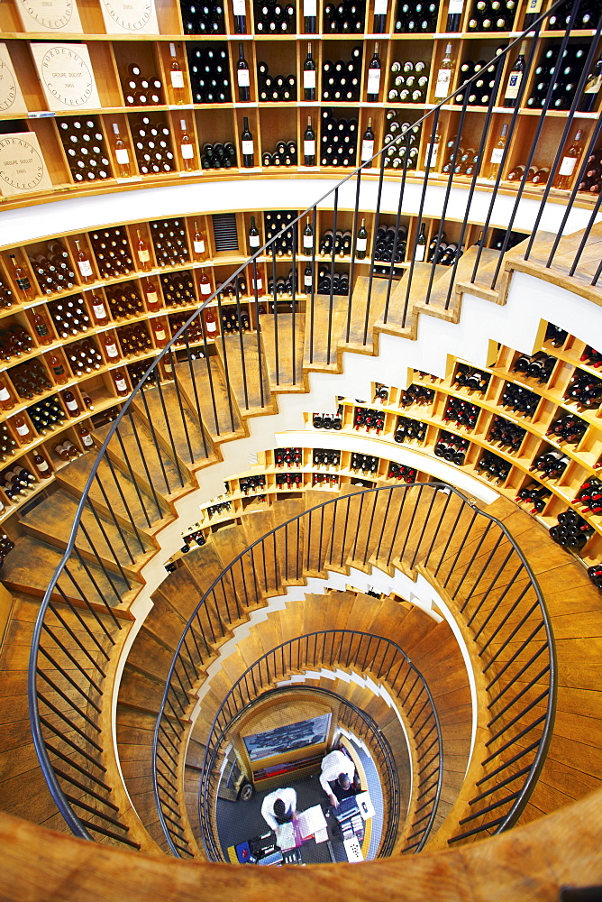 Spiral staircase with wine bottles kept on rack in L'Intendant wine shop, Bordeaux, France