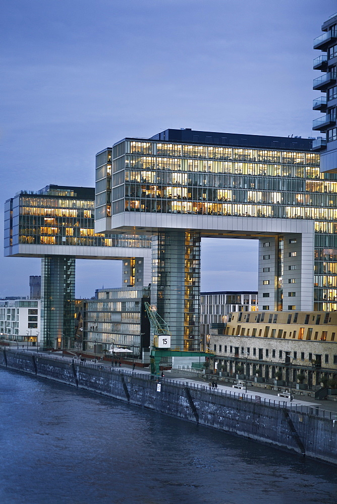 View of illuminated glass building with river at side in Rheinauhafen, Cologne, Germany
