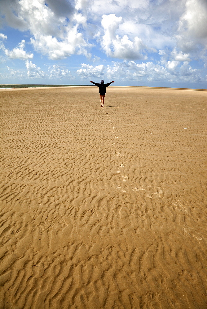 Person walking on the rippled sand at Fano beach, Denmark