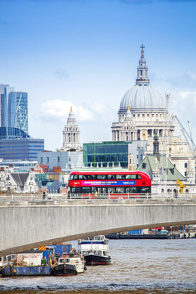 London bus crossing Waterloo bridge with the dome of St. Paul's behind