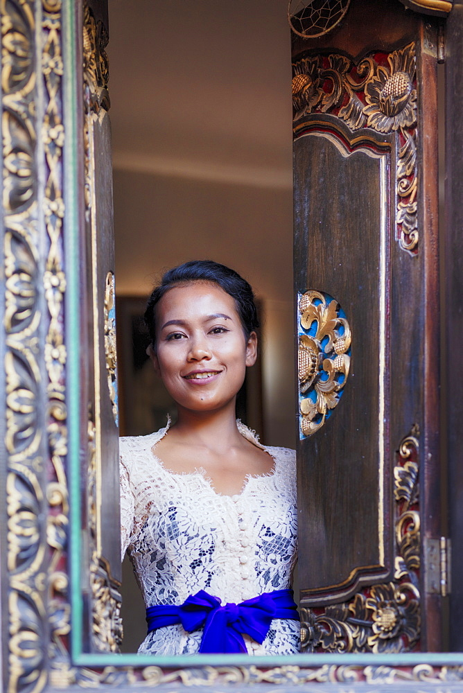 Indonesia, Bali. A Balinese woman in traditional dress looking out from a carved window in a local village