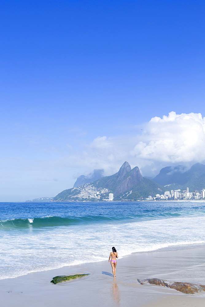 A 20-25 year old young Brazilian woman on Ipanema Beach with the Morro Dois Irmaos hills in the distance, Rio de Janeiro, Brazil, South America