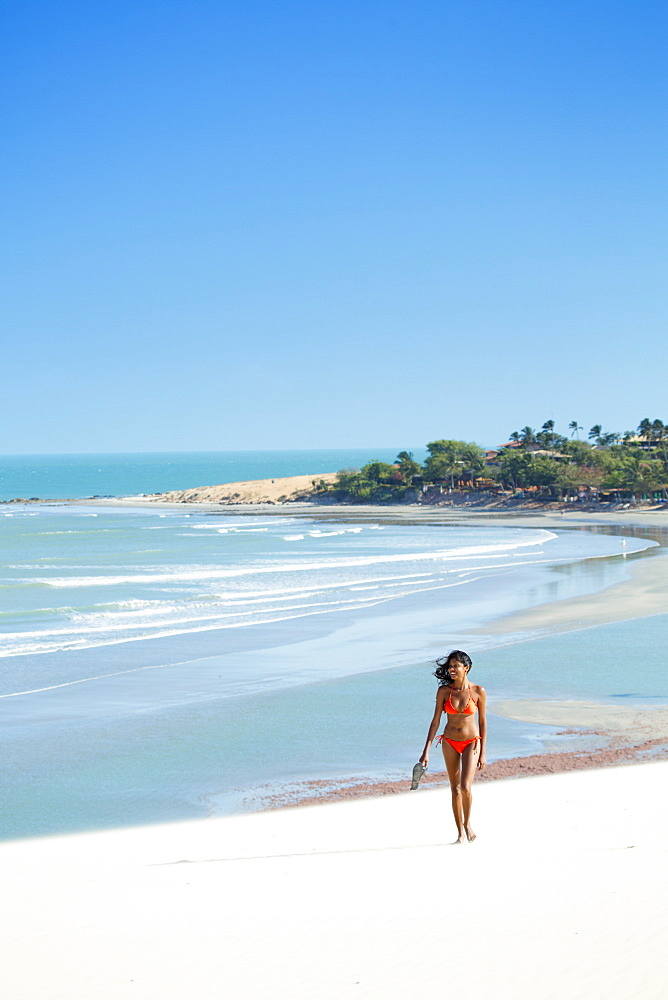 A young woman walking along the beach in Jericoacoara, Ceara, Brazil, South America