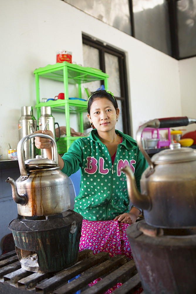 Local woman preparing tea in a huge kettle, Mandalay, Myanmar, Southeast Asia