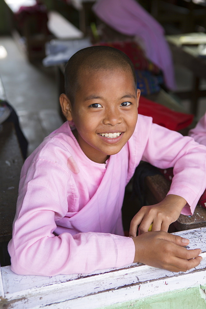 Buddhist novice schoolgirl sitting at her desk in the school classroom, Sagaing, Myanmar, Southeast Asia