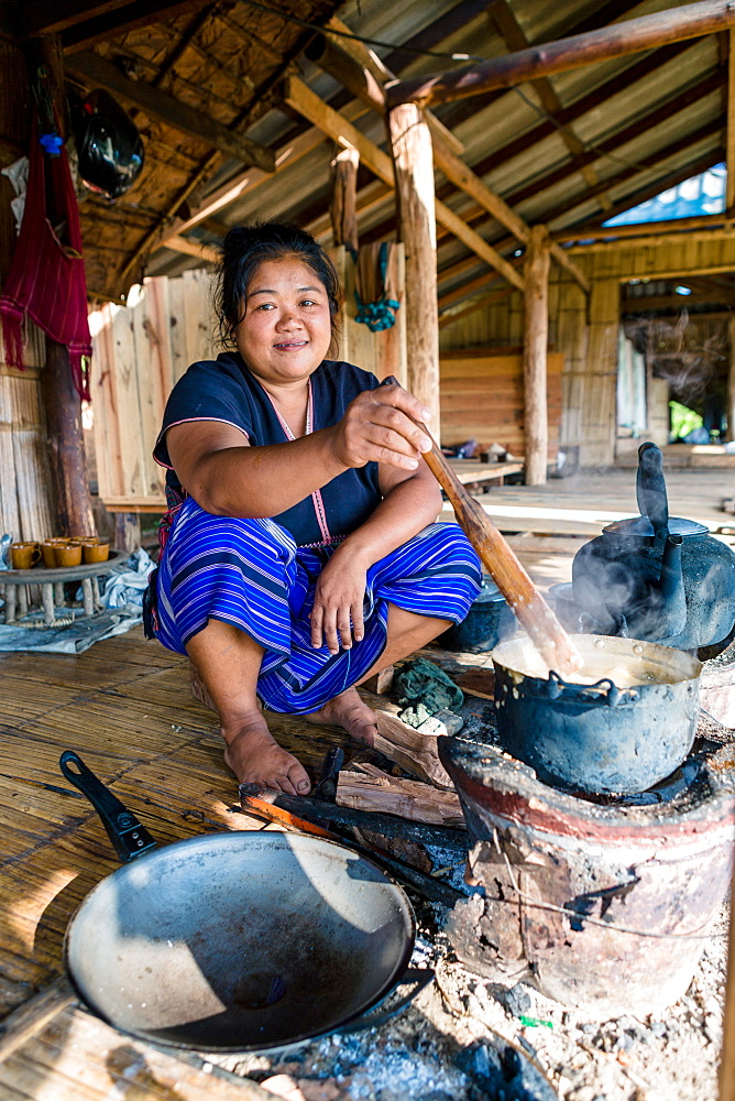 Indigenous White Karen (Kayin) hill tribe villager cooking at a traditional stove in a mountain village near Doi Inthanon, Chiang Mai, Thailand, Southeast Asia, Asia
