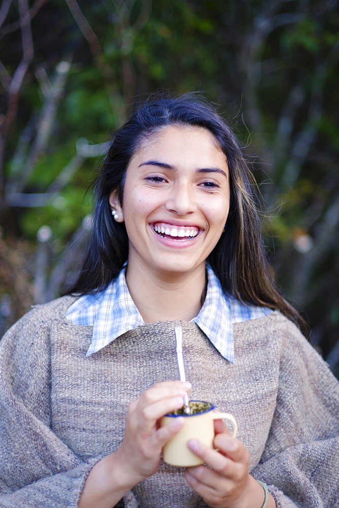 A Patagonian girl in a traditional wool poncho with a bombilla straw drinking yerba mate