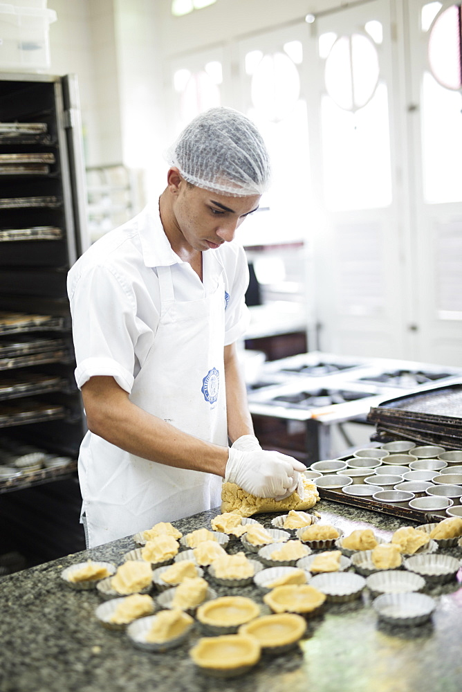 A baker making Portuguese custard tarts in the Confeitaria Colombo, a famous cafe in central Rio de Janeiro, Brazil, South America