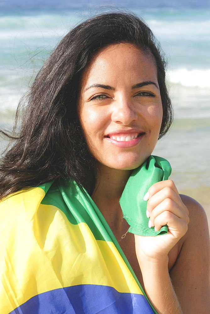 Young Brazilian woman, 20 to 29 years old, wrapped in the Brazilian flag on a beach in Rio de Janeiro, Brazil, South America