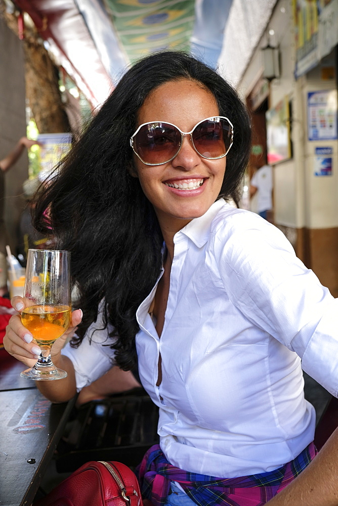Young Brazilian woman, 20 to 29 years old, with a beer in an open-air bar in central Rio de Janeiro, Brazil, South America