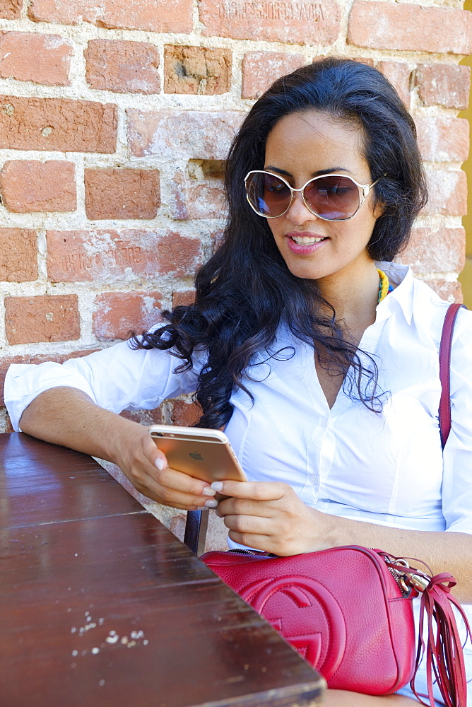 Young Brazilian (Latin American) (Latina) woman, 20 to 29 years old using her mobile phone in a cafe, Rio de Janeiro, Brazil, South America