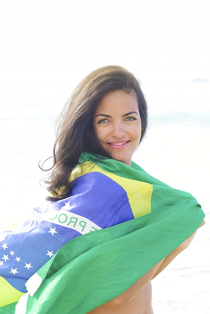 Young Brazilian woman 20 to 29 years old with a Brazilian flag beach wrap on a beach, Rio de Janeiro, Brazil, South America