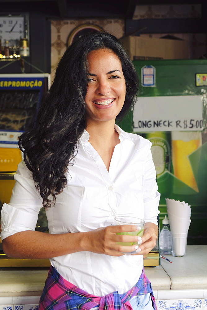 Young Brazilian woman 20 to 29 years old in a bar holding a caipirinha cocktail, Rio de Janeiro, Brazil, South America