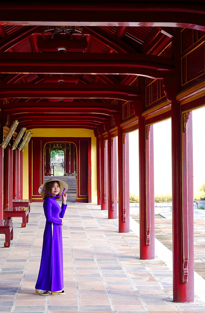 A woman in a traditional Ao Dai dress and Non La conical hat in the Forbidden Purple City of Hue, UNESCO World Heritage Site, Thua Thien Hue, Vietnam, Indochina, Southeast Asia, Asia - 1176-822