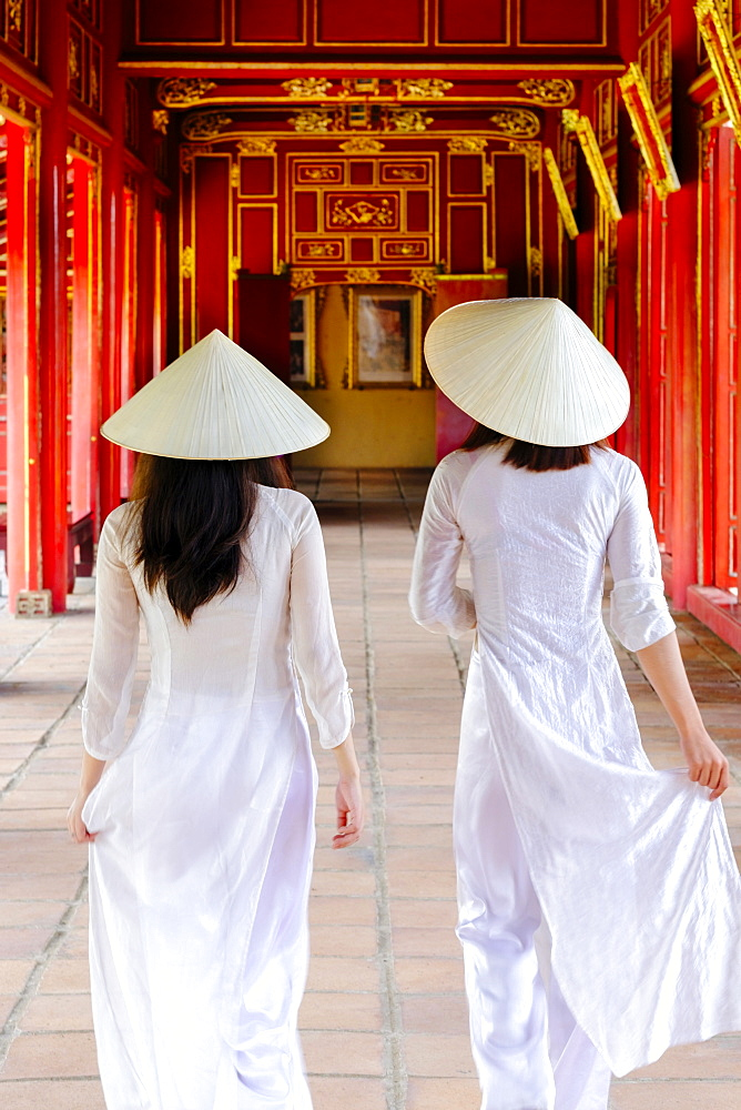 Two Vietnamese women in traditional Ao Dai dresses and Non La conical hats in the Forbidden Purple City of Hue, Thua Thien Hue, Vietnam, Indochina, Southeast Asia, Asia - 1176-824