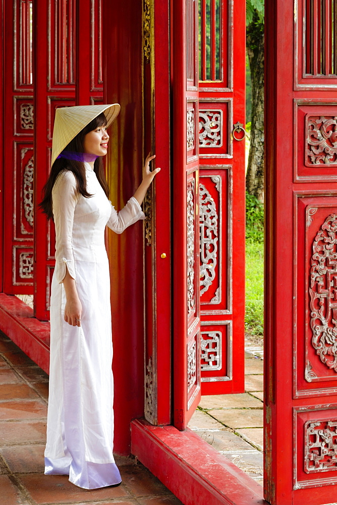 A woman in a traditional Ao Dai dress and Non La conical hat in the Forbidden Purple City of Hue, UNESCO World Heritage Site, Thua Thien Hue, Vietnam, Indochina, Southeast Asia, Asia - 1176-825