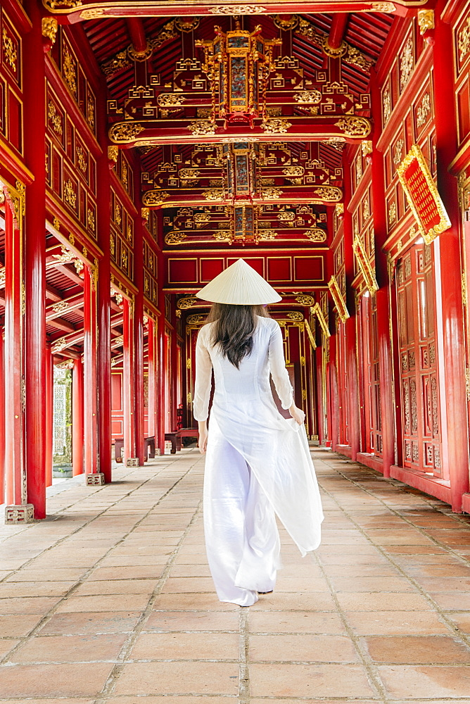 A woman in a traditional Ao Dai dress and Non La conical hat in the Forbidden Purple City of Hue, UNESCO World Heritage Site, Thua Thien Hue, Vietnam, Indochina, Southeast Asia, Asia - 1176-835