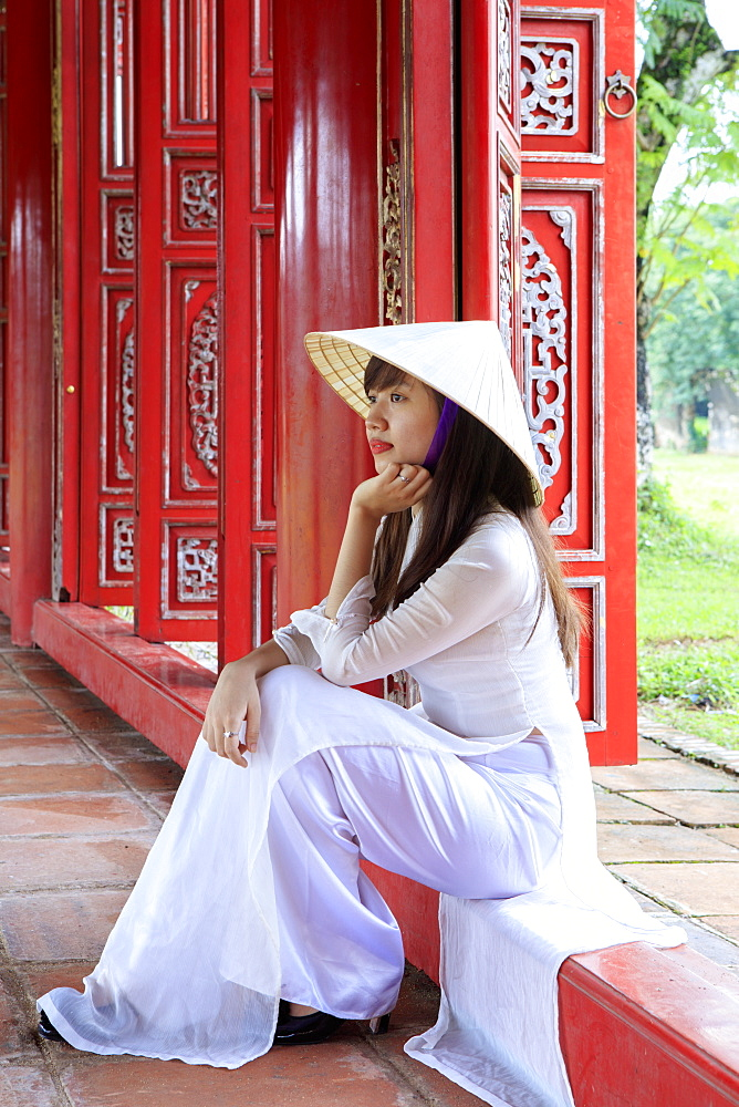 A woman in a traditional Ao Dai dress and Non La conical hat in the Forbidden Purple City of Hue, UNESCO World Heritage Site, Thua Thien Hue, Vietnam, Indochina, Southeast Asia, Asia - 1176-836
