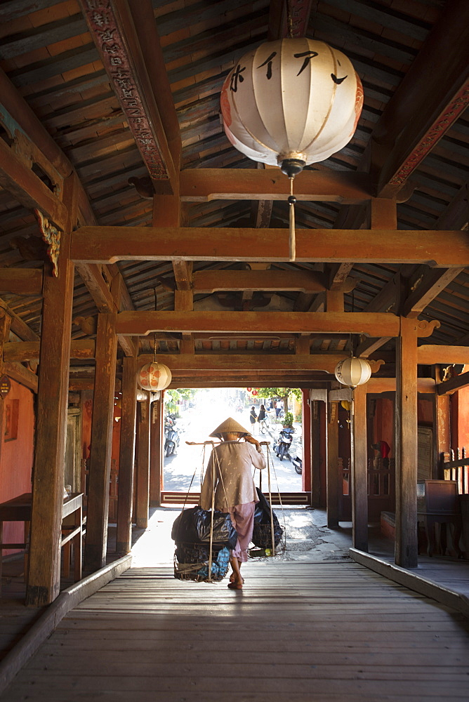 A woman carrying bags on a hod through the covered Japanese bridge in Hoi An, Quang Nam, Vietnam, Indochina, Southeast Asia, Asia - 1176-838