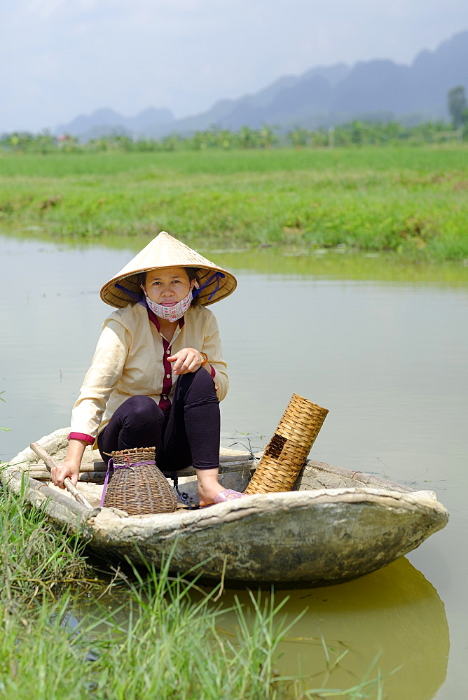 Local village fisherwoman wearing a Non La conical hat and sitting in a concrete lined bamboo boat, Ninh Binh, Vietnam, Indochina, Southeast Asia, Asia