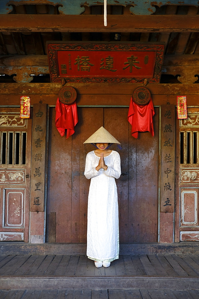 A young woman in a Non La conical hat and a traditional Ao Dai dress in the historical centre, Hoi An, Quang Nam, Vietnam, Indochina, Southeast Asia, Asia