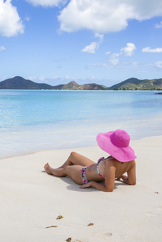 Lady on the sand surrounded by turquoise Caribbean Sea, Ffryes Beach, Sheer Rocks, Antigua and Barbuda, Leeward Islands, West Indies, Caribbean, Central America