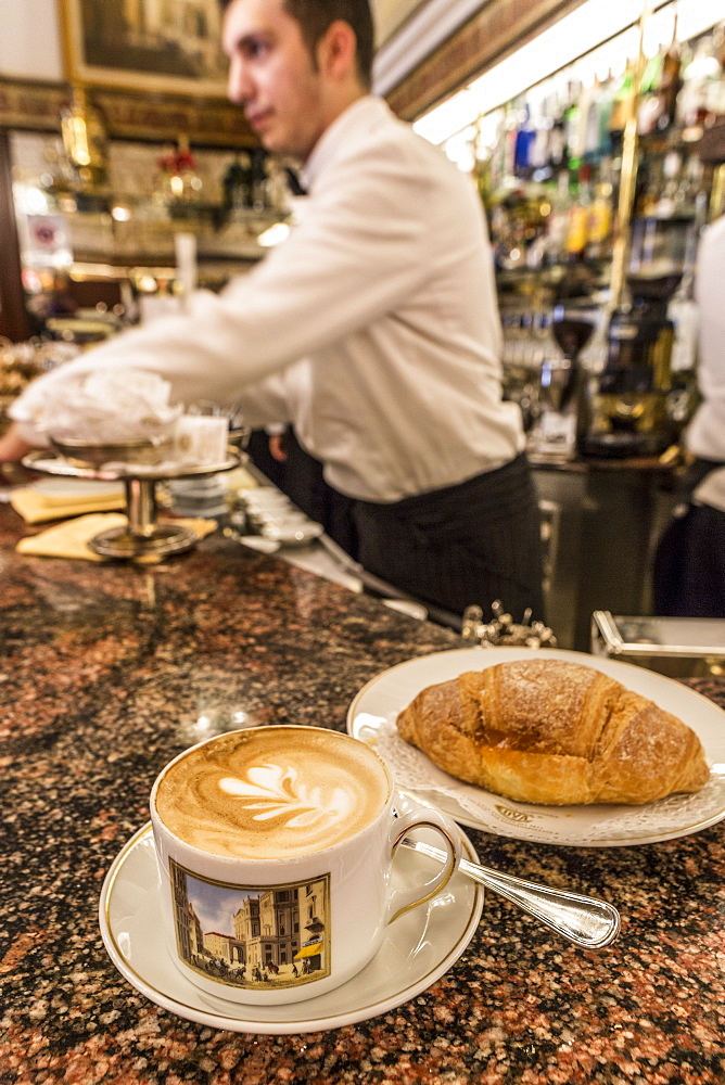 The typical Milanese breakfast with cappuccino and homemade brioche at the old Cafe Cova, icon of Milan, Lombardy, Italy, Europe