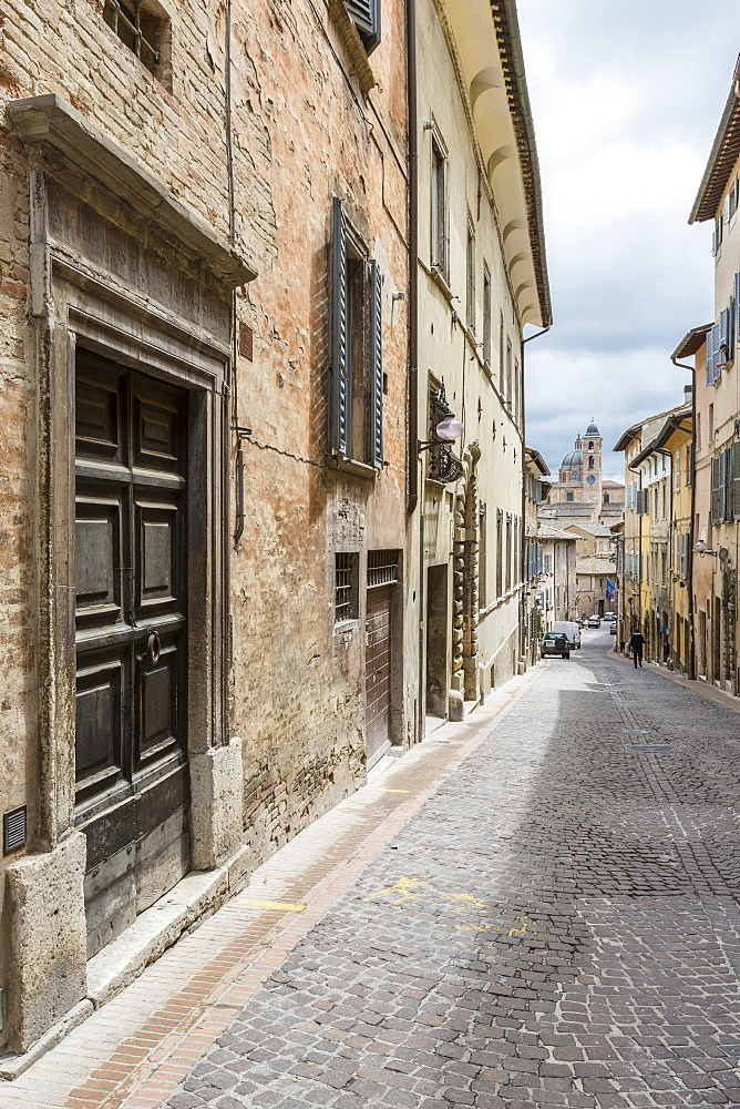 A medieval alley of the hill town with Piazza Duca Federico in the background, Urbino, Province of Pesaro, Marche, Italy, Europe
