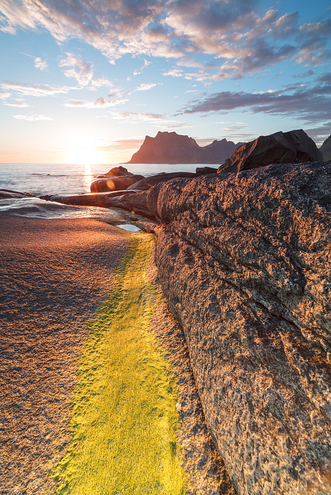 Lights of the midnight sun on the rocks surrounding the blue sea, Uttakleiv, Lofoten Islands, Northern Norway, Scandinavia, Europe