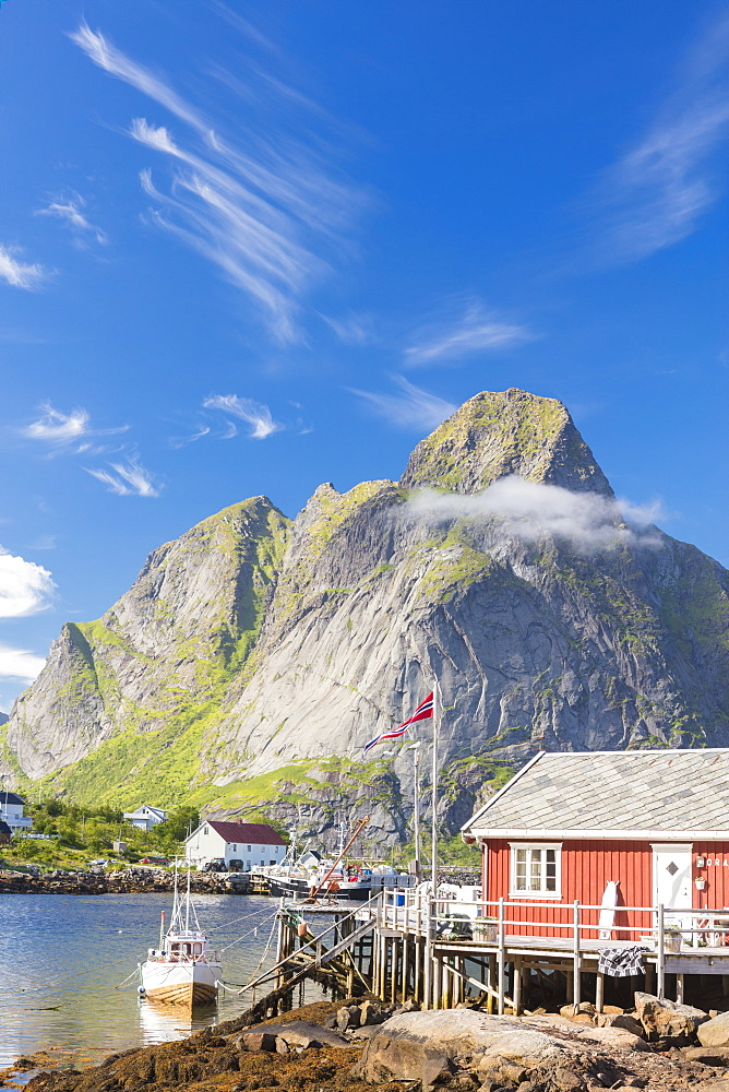 Typical house of fishermen called Rorbu framed by rocky peaks and blue sea, Reine, Moskenesoya, Lofoten Islands, Norway, Scandinavia, Europe