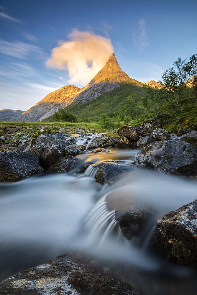 Waterfall frames the Stetinden mountain peak illuminated by midnight sun Tysfjord Norway Europe