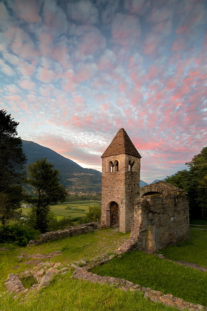 Pink clouds at sunset on the old Abbey of San Pietro in Vallate, Piagno, Sondrio province, Lower Valtellina, Lombardy, Italy, Europe