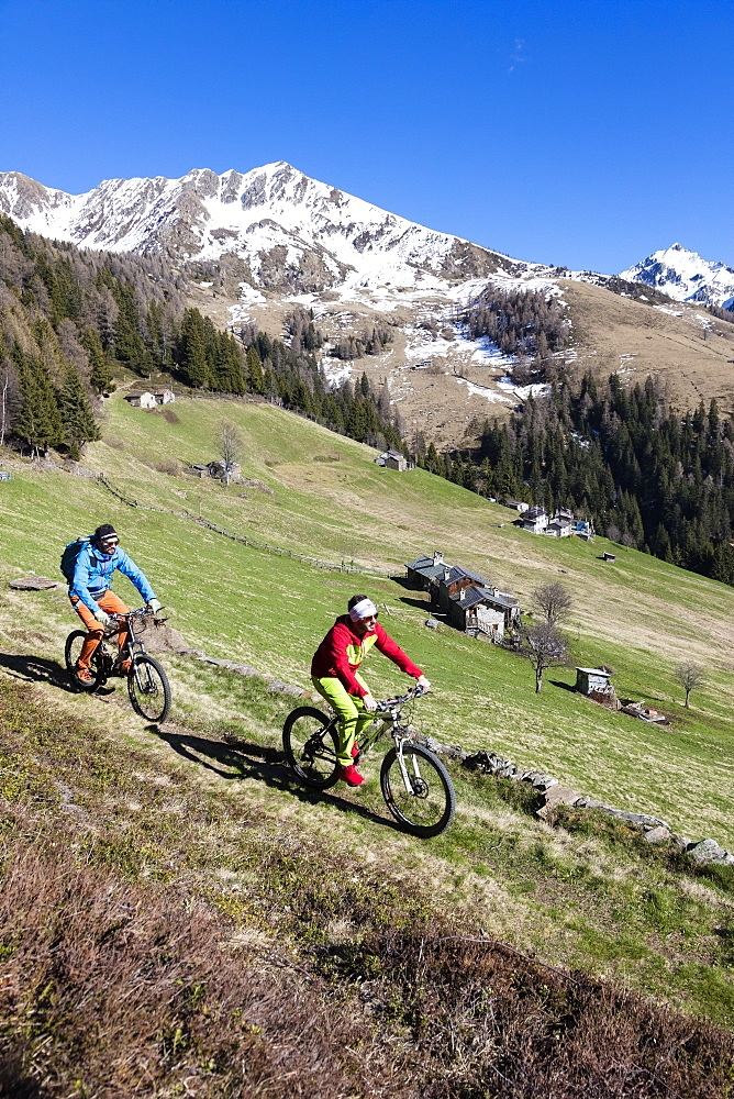 Mountain bikes on green meadows framed by snowy peaks in spring Albaredo Valley Orobie Alps Valtellina Lombardy Italy Europe