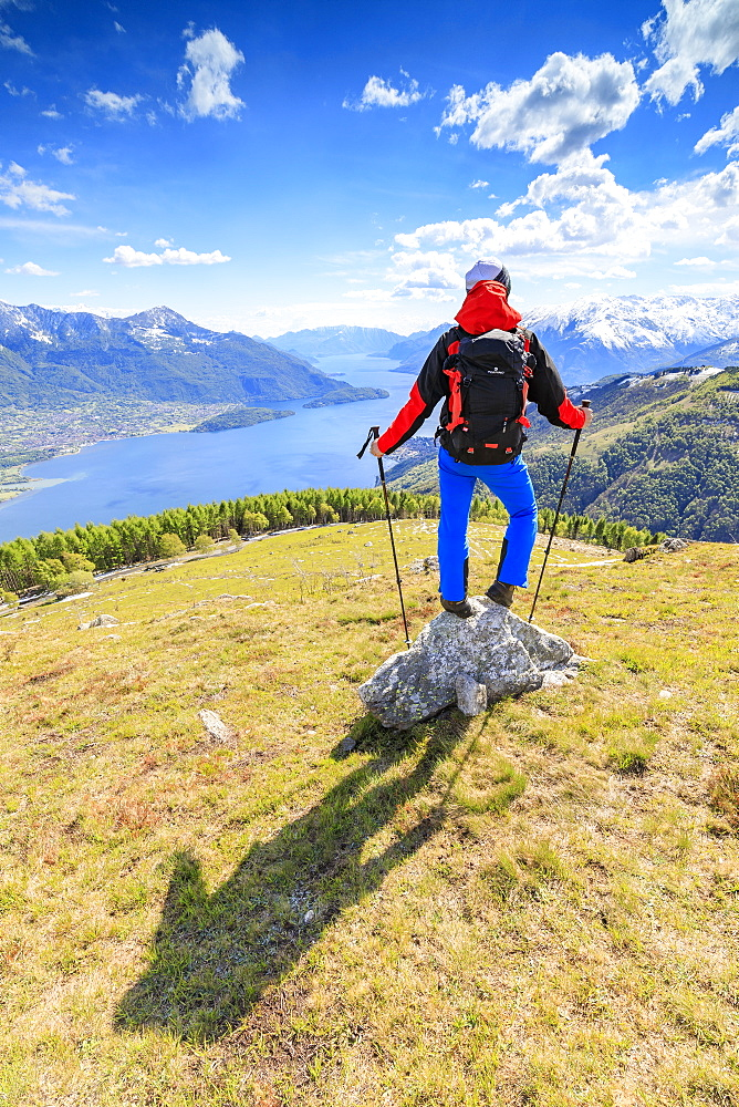 Hiker on green meadows admires Lake Como surrounded by woods Montemezzo Alpe Zocca Lombardy Italy Europe