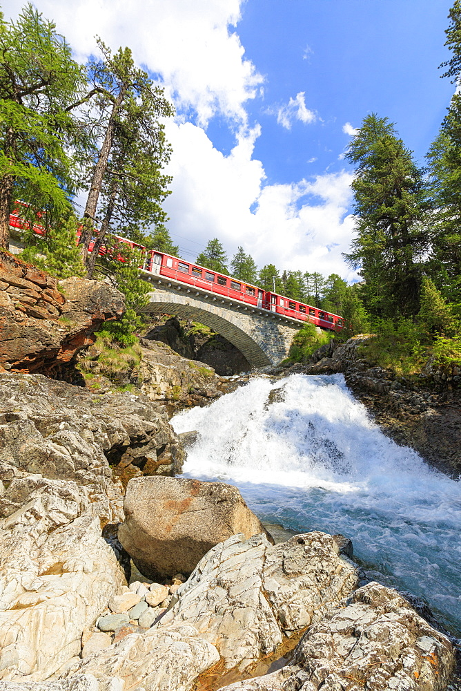Bernina Express train above an alpine creek, Morteratsch, Engadine, Canton of Graubunden, Switzerland, Europe
