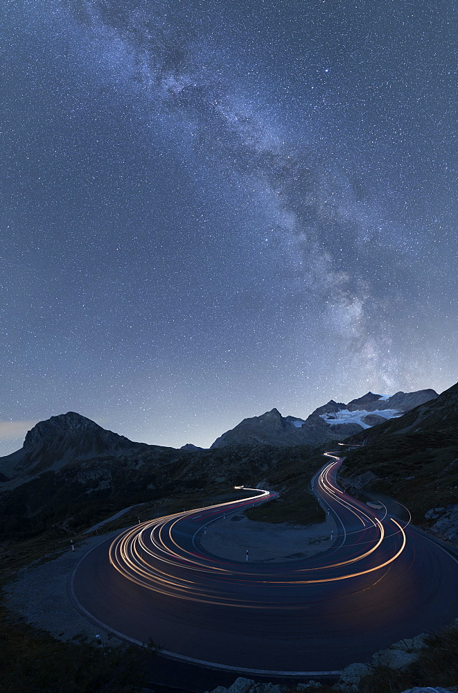 Milky Way and lights of car traces, Bernina Pass, Poschiavo Valley, Engadine, Canton of Graubunden, Switzerland, Europe