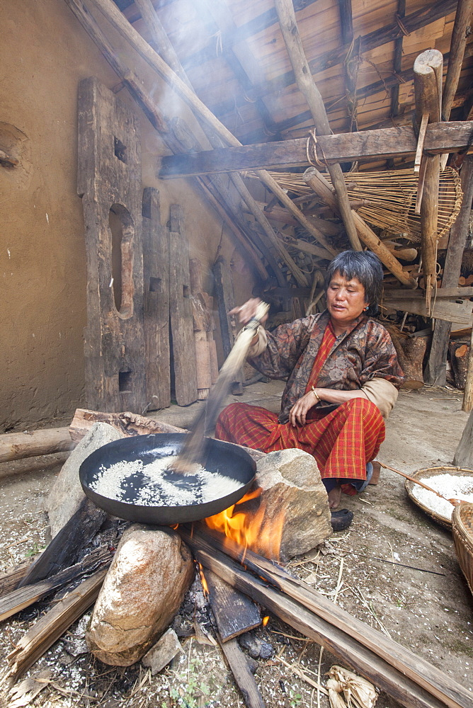 Old woman of Thimphu with traditional clothes cooking rice for lunch in a simple wooden house, Bhutan, Asia